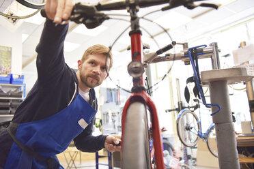 Bicycle mechanic working in his repair shop - LYF00814