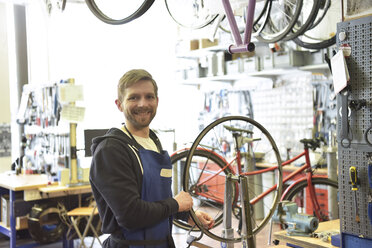 Bicycle mechanic in his repair shop, portrait - LYF00817