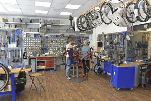 Salesperson helping customer in bicycle shop - LYF00823