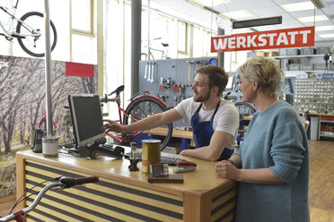 Salesperson helping customer in bicycle shop - LYF00826