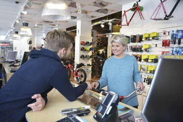 Salesperson helping customer in bicycle shop - LYF00832