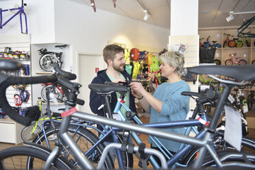 Salesperson helping customer in bicycle shop - LYF00835