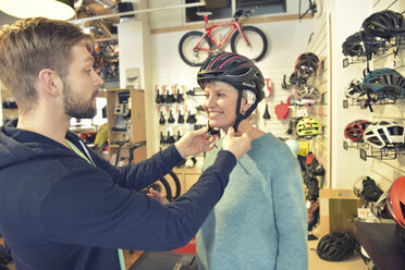 Salesperson helping customer with bicycle helmet - LYF00838