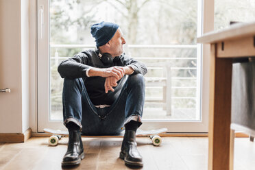 Cool senior man sitting on ground, looking out of window - GUSF00673