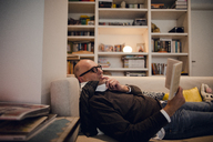 Senior man lying on couch, reading book - GUSF00676