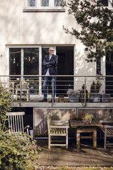 Senior man standing on his veranda, looking proud - GUSF00682