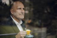 Senior businessman standing by window, drinking coffee - GUSF00694