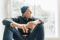 Cool senior man sitting on longboard, looking out of window - GUSF00697