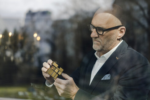 Senior businessman putting together puzzle cube - GUSF00712