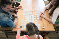 Family playing memory on table at home - MOEF01070