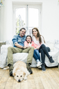 Portrait of happy family with dog in living room - MOEF01076