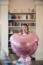 Portrait of girl with braids holding big heart-shaped balloon - MOEF01079