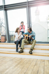 Happy family on stairs outside making music together - MOEF01085