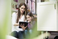 Mother and daughter using tablet together at home - MOEF01094