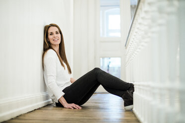 Portrait of smiling woman at home sitting on the floor - MOEF01100