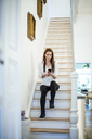 Smiling woman sitting on stairs at home using cell phone - MOEF01103