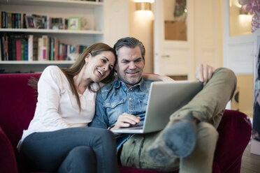 Happy couple sitting on couch using laptop - MOEF01109