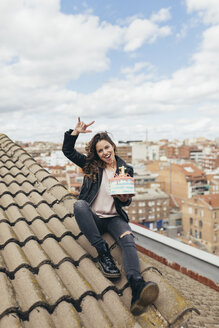Laughing woman sitting on roof with Birthday cake showing Rock And Roll Sign - JPF00308