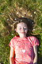 Portrait of smiling girl lying on grass in spring with daisies on hair - SARF03679