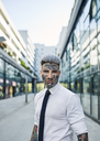 Young businessman with tattooed face walking in the city, portrait - ZEDF01330