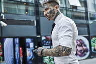Young businessman with tattooed face using smartphone - ZEDF01333
