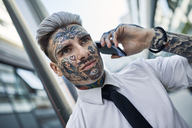 Young businessman with tattooed face, talking on he phone - ZEDF01336