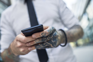Young businessman with tattooed face using smartphone - ZEDF01339