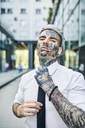 Young businessman with tattooed face, fastening tie - ZEDF01348
