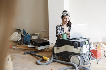 Young woman renovating her new flat, using laptop - PESF01069