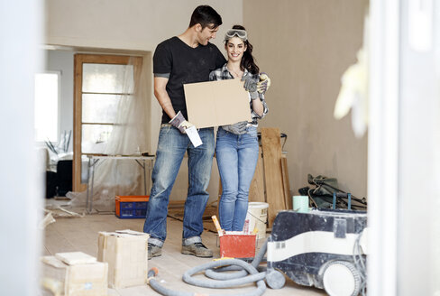 Happy couple renovating their new home, holding cardboard sign - PESF01081