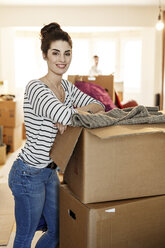 Young woman moving house, unpacking cardboard boxes - PESF01087