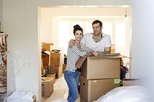 Young couple moving house, unpacking cardboard boxes - PESF01090