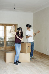 Couple moving into their new home, looking through VR glasses - PESF01093