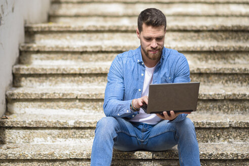 Young man sitting on stairs, working, using laptop - JSMF00146