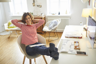 Portrait of smiling mature woman relaxing on armchair at home office - PNEF00625