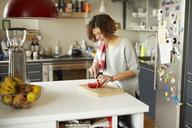 Mature woman cutting tomato in kitchen - PNEF00634