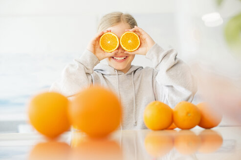 Laughing girl covering her eyes with halves of orange - NEKF00031