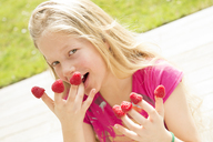 Portrait of smiling girl with raspberries on  fingers - NEKF00037