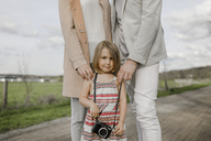 Portrait of smiling little girl with parents standing behind her - KMKF00236