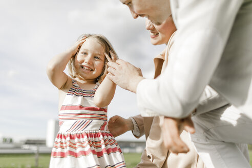 Portrait of happy little girl with her parents outdoors - KMKF00239