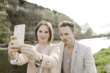Portrait of young couple taking selfie with smartphone outdoors - KMKF00245