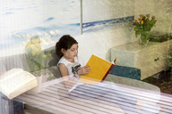 Girl sitting on the couch at home reading a book - NEKF00040