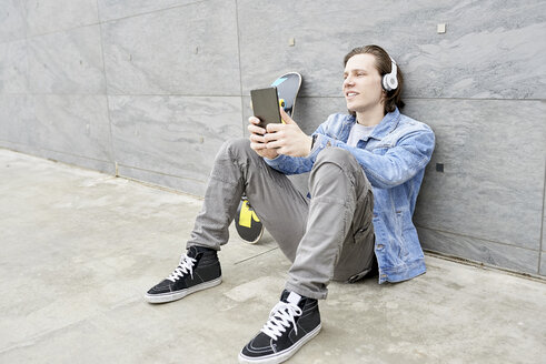 Young man with skateboard sitting on ground, using digital tablet - FMOF00367