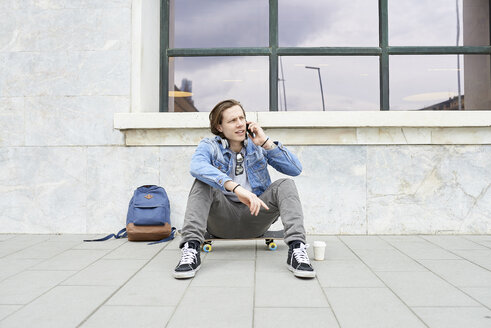Young man with skateboard sitting on ground, using smartphone - FMOF00376