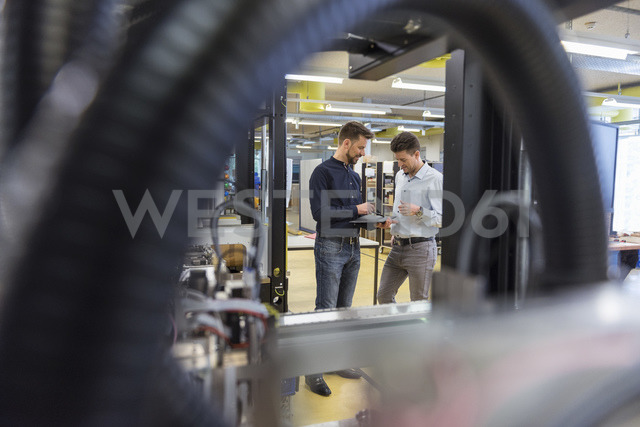 Two men with tablet talking in factory - DIGF03977