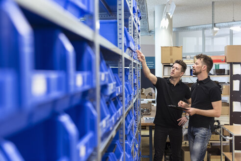 Two men talking in factory storeroom - DIGF04019