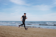 Spain, man dressed in black jogging on the beach - RTBF01220