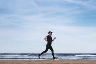 Spain, man dressed in black jogging on the beach - RTBF01223