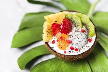 Coconut bowl with variuos fruits, natural yoghurt and seeds on leaf - RTBF01229