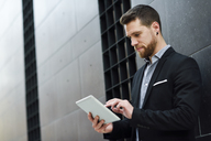 Young businessman looking at his digital tablet - JSMF00152